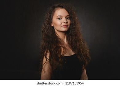 People, beauty and lifestyle concept. Isolated shot of mysterious young female with black eyes and voluminous dark hair looking at camera with smile. Charming brunette woman having pensive look