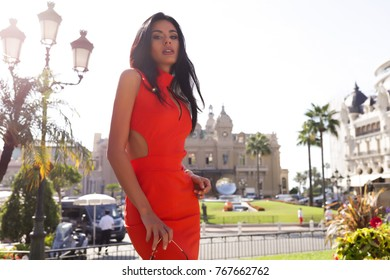 People, beauty and lifestyle concept. Shot of attractive sensual woman with wide smile dressed in red dress and wear gold watch smiling broadly being happy to meet her best friend. Joyful nice female
