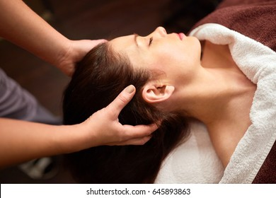 people, beauty, lifestyle and relaxation concept - beautiful young woman lying with closed eyes and having head massage at spa