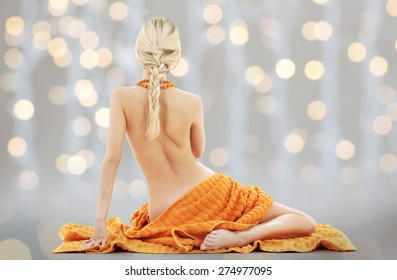 people, beauty, sexuality and erotic concept - beautiful young woman with orange towel over holidays lights background