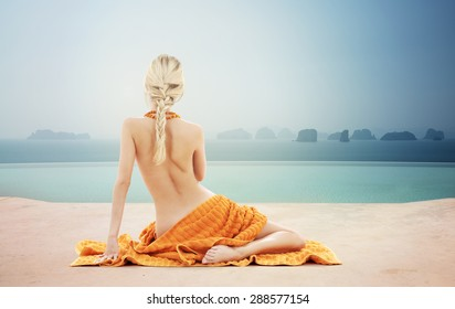 people, beauty, sexuality, luxury and travel concept - beautiful young woman with orange towel over infinity pool and sea background