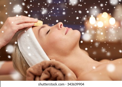 people, beauty, spa, cosmetology and relaxation concept - close up of beautiful young woman lying with closed eyes having face cleaning by sponge and beautician hand in spa salon with snow effect