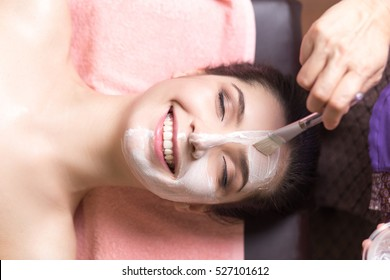 people, beauty, spa, cosmetology and skincare concept - close up of beautiful young woman lying with closed eyes and cosmetologist applying facial mask by brush in spa center