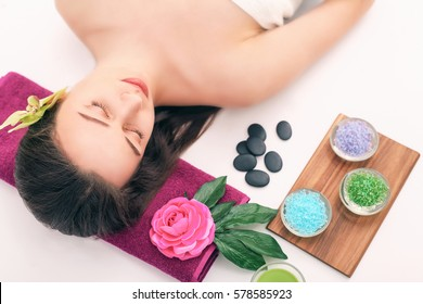 people, beauty, spa, cosmetology and skincare concept - close up of beautiful young woman lying with closed eyes and cosmetologist applying facial mask by brush in spa.