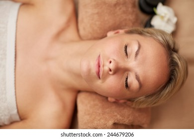 people, beauty, spa, healthy lifestyle and relaxation concept - close up of beautiful smiling young woman lying with closed eyes in spa