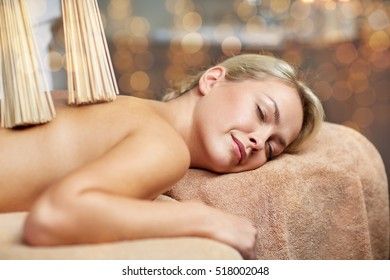 people, beauty, spa, healthy lifestyle and relaxation concept - close up of beautiful young woman lying with and having samurai massage with bamboo brooms in spa