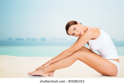 people, beauty, spa and resort concept - beautiful woman in cotton underwear touching her legs over infinity edge pool background