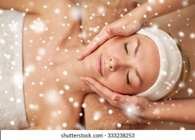 people, beauty, spa, winter and relaxation concept - close up of beautiful young woman lying with closed eyes and having face massage in spa with snow effect