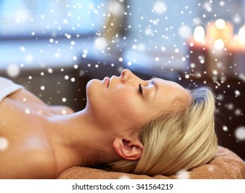 people, beauty, spa, winter and relaxation concept - close up of beautiful smiling young woman lying with closed eyes in spa salon with snow effect