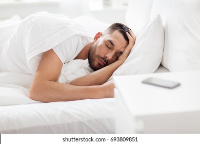 people, bedtime and rest concept - man sleeping in bed at home with smartphone on nightstand