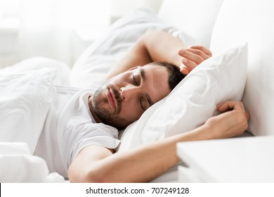 people, bedtime and rest concept - man sleeping in bed at home