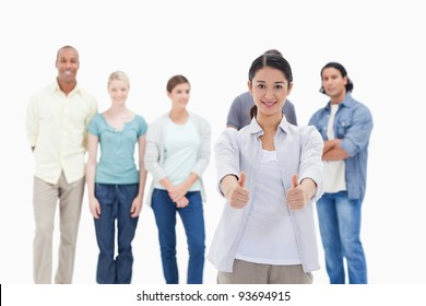 People behind a woman smiling with her the thumbs-up against white background