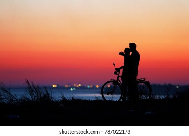 people with bicycles at sunset by the sea