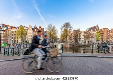 People bicycling through city streets on a beautiful summer day in Amsterdam, Netherlands.