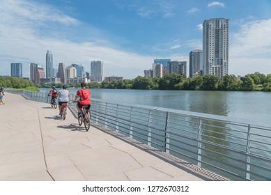 People biking running walking along Colorado River waterfront boardwalk near downtown Austin, Texas in summer day