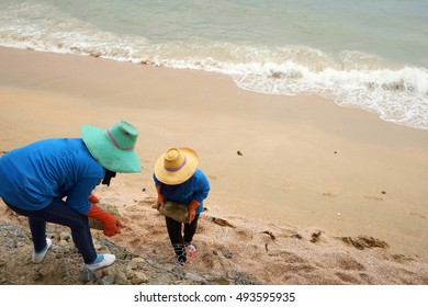 People with blue shirt and hat work at barrier stone for protection strong wave from the sea.