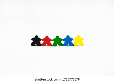 People for board games are on a white background. They are of different colors. Wooden toy people symbolize friendship, tolerance and unity.