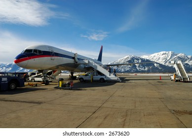 People Boarding a Jet Airplane with snow covered mountains in background