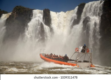 People in boat to see the waterfalls up close - Iguazu Warterfalls National Park, a wonder of nature between Brazil and Argentina