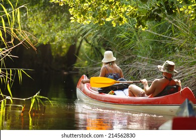 People boating on small river full of water lilies and having fun