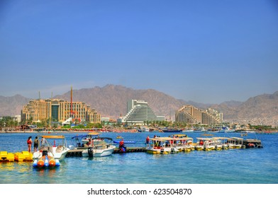 People and boats in a pier in Eilat in the background of the new harbor of Eilat with its beautiful resorts, Israel.