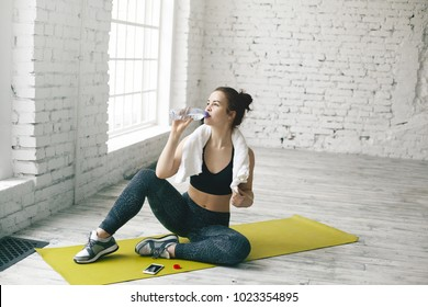 People, body shape, health, wellbeing and active lifestyle concept. Successful fit young businesswoman in sportswear having rest and drinking water during workout on mat before going to office