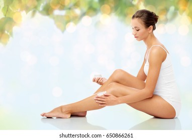 people, bodycare and beauty concept - beautiful woman applying moisturizing cream to her leg over natural green background and lights