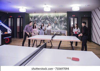 People break playing table tennis relax in office lounge with company colleagues
