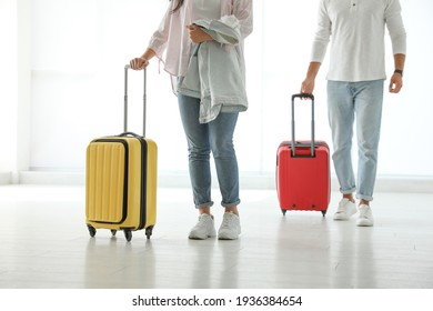 People with bright travel suitcases in airport