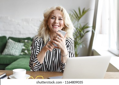People, business, age and modern gadgets concept. Cheerful successful sixty year old blonde self-employed woman working from home, using generic electronic devices, enjoying online cmmunication