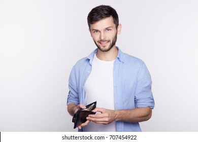 People, business, finances, money concept. Close up studio shot of young Caucasian confident businessman dressed casual holding open wallet with cash and happy smile on his face. Well-being concept.