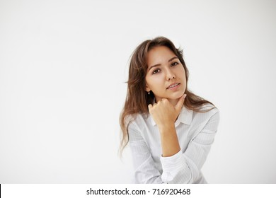 People, business and modern lifestyle concept. Headshot of pensive beautiful young female entrepreneur with long dark hair touching her chin while posing at white wall, having thoughtful look