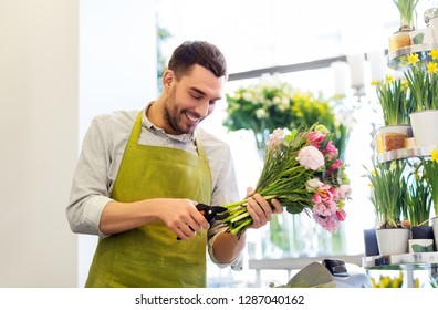 people, business, sale and floristry concept - happy smiling florist man making bunch at flower shop