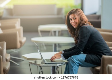People, Business and Technology concept - Smiling asian woman with laptop computer sitting at table over office window background.