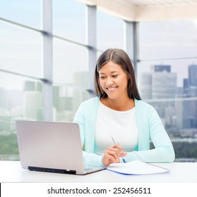 people, business and technology concept - smiling woman in with laptop computer and notebook sitting at table over office window background