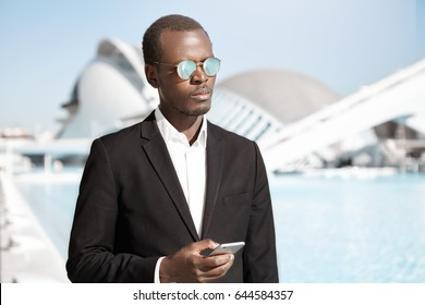 People, business, technology concept. Young elegant handsome dark-skinned manager of company dressed in black formal suit waiting for meeting while standing against metropolis background holding phone
