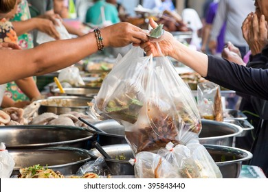 People buy and sell food at a stall in a morning grocery market in Thailand