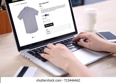 People buying casual shirt on ecommerce website with smart phone, credit card and coffee on wooden desk