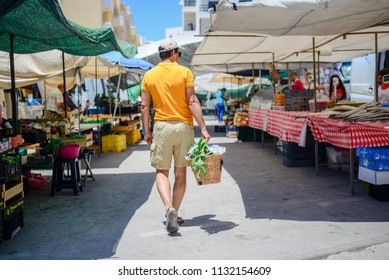 People buying fruits and vegetables. Back view of man on summer outdoors farm market shopping background. Real purchasing selling natural healthy lifestyle candid closeup image.