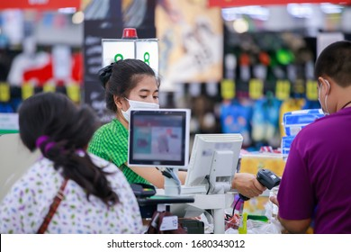 People buying goods in a grocery store.Cashier or supermarket staff and customers in medical protective mask.covid-19 spreading outbreak