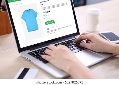 People buying running shirt on ecommerce website with smart phone, credit card and coffee on wooden desk