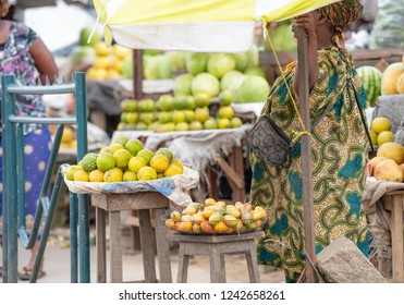 People buying and selling food at grand market in Douala, Cameroon. West-African and Central-African traditional clothes and colors.