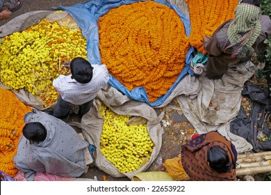 People buying and selling orange and yellow flowers and garlands at the flower market in Kolkata, West Bengal, India