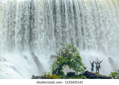People by waterfall Sae Pong Lai waterfall on Laos golden circle. Couple visiting famous tourist attractions and landmarks in Laos nature landscape.