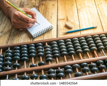 People are calculated using old abacus and note down with a pencil on wood table