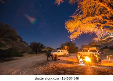 People camping by side the campfire and under the stars next to the mountains of Spitzkoppe-Namibia.