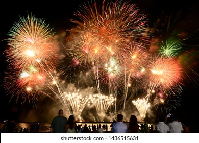 People capturing a fireworks shows with their mobile phone. Colorful fireworks celebration and the night sky background with crowded people on the beach.