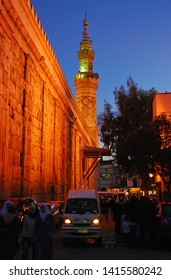 People and cars pass by The Umayyad Mosque / Great Mosque of Damascus /. The mosque has spectacular and beautiful lighting. Syria before the war. Damascus, Syria, Middle East. November 22, 2007.