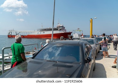 People and cars are waiting for approaching red ferryboat. Cars are reverse position in line because port is very narrow.