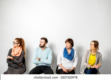 People in casual clothes waiting in a line on the white wall background